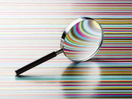 Magnifying glass leaning on striped background LANG_EVOIMAGES