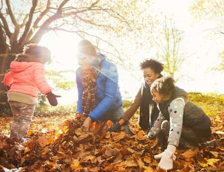 Young family playing in autumn leaves in sunny park