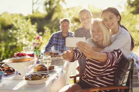 alcohol series: Mother and daughters taking selfie with camera phone at garden party patio table