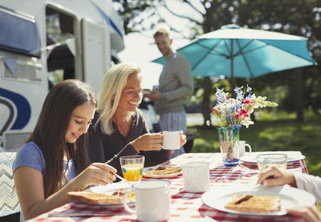 family: Smiling mother and daughter enjoying breakfast outside sunny motor home