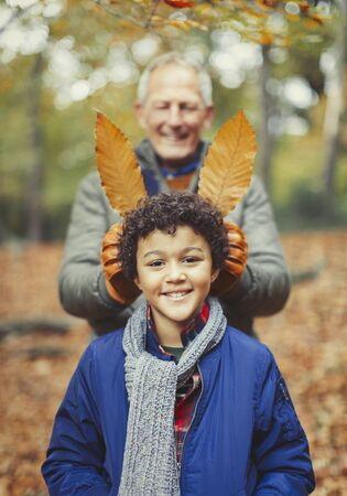 Grandfather holding autumn leaves behind grandson in woods