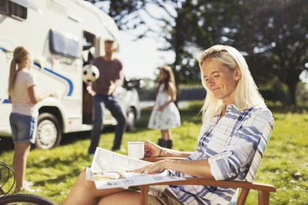 transportation: Smiling woman reading magazine and drinking coffee outside sunny motor home