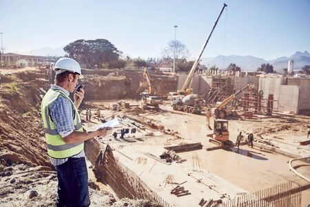 incidental people: Construction worker foreman using walkie-talkie at sunny construction site