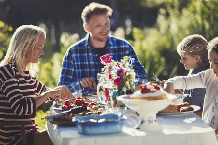 family: Family eating at sunny garden party patio table