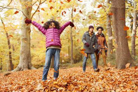 brazilian ethnicity: Playful girl throwing autumn leaves in woods