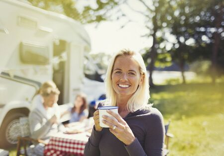campsite: Portrait smiling woman drinking coffee outside sunny motor home LANG_EVOIMAGES