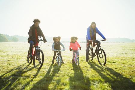 brazilian ethnicity: Portrait young family bike riding in sunny autumn park grass LANG_EVOIMAGES