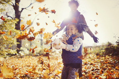Playful mother and daughter throwing autumn leaves in sunny park LANG_EVOIMAGES