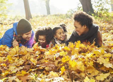 Playful young family laying in autumn leaves in sunny woods LANG_EVOIMAGES