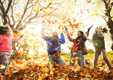 Playful young family throwing autumn leaves in sunny park