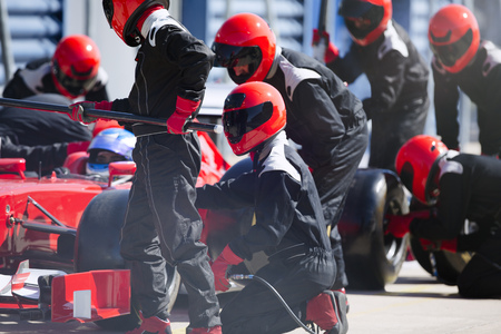Pit crew replacing tires on formula one race car in pit lane