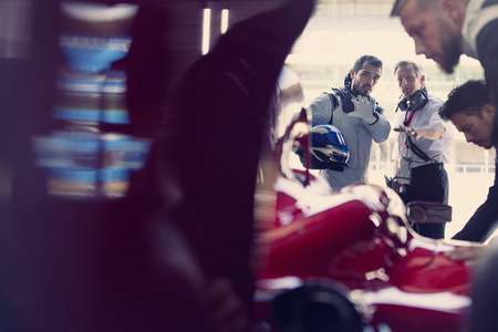 formula one: Manager and formula one race car driver talking in repair garage LANG_EVOIMAGES
