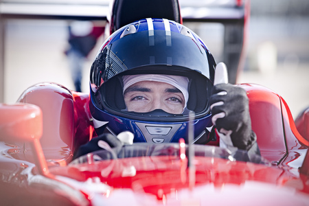visualizing: Portrait confident male formula one race car driver gesturing thumbs-up