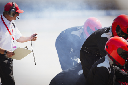 career timing: Manager with stopwatch timing formula one pit crew practice session