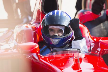 Formula one race car driver in helmet gesturing, celebrating victory LANG_EVOIMAGES