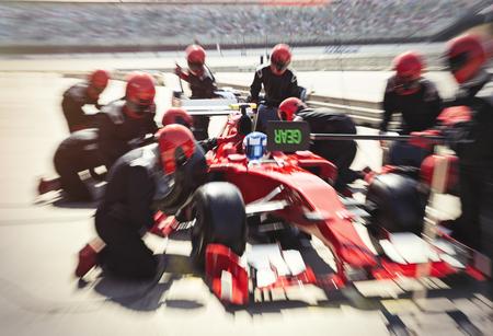 arrodillarse: Equipo de pozo reemplazando neumáticos en un coche de carreras de Fórmula 1 en el carril de boxes