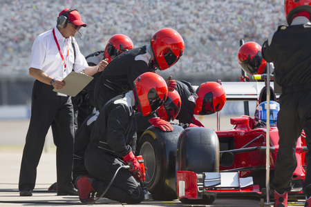 Manager with stopwatch timing pit crew replacing formula one race car tire in pit lane