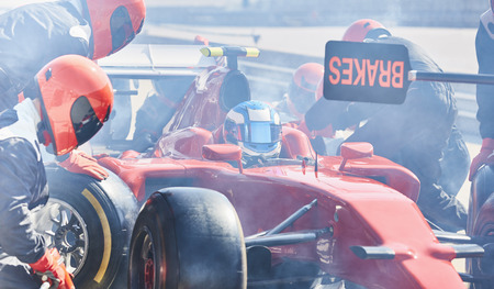 one lane sign: Pit crew replacing tires on formula one race car in pit lane