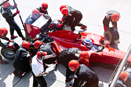 Manager with stopwatch timing pit crew replacing tires in pit lane
