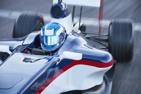 formula one: Formula one race car driver in helmet on sports track
