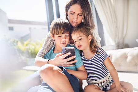 Mother and children using cell phone in sunny living room LANG_EVOIMAGES