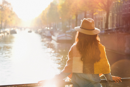 Woman looking at sunny autumn canal view, Amsterdam LANG_EVOIMAGES