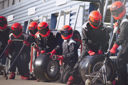 formula one: Pit crew ready with tires in formula one pit lane