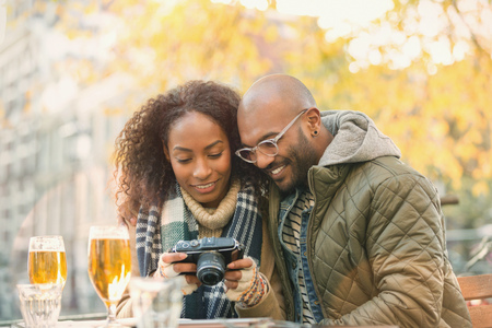 Young couple viewing digital camera and drinking beer at autumn sidewalk cafe LANG_EVOIMAGES