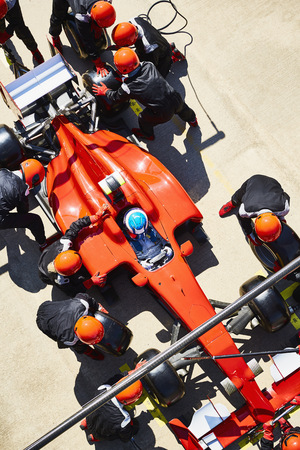 Overhead pit crew replacing tires on formula one race car in pit lane LANG_EVOIMAGES