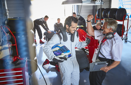 Driver and formula one race car driver cheering, celebrating victory in repair garage LANG_EVOIMAGES