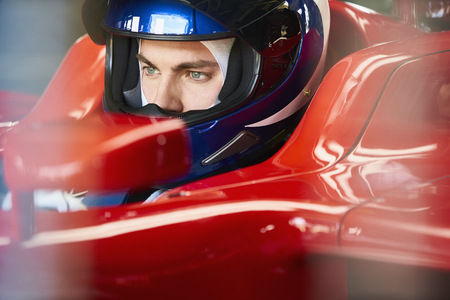 formula one: Close up focused formula one driver wearing helmet in race car