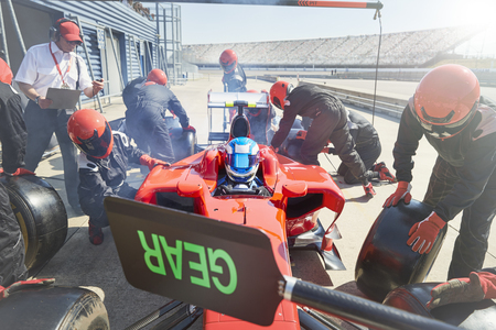 career timing: Pit crew replacing tires on formula one race car in pit lane