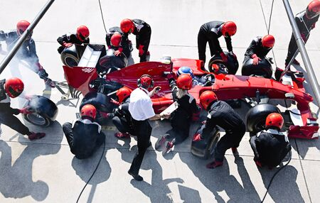 career timing: Manager with stopwatch timing pit crew replacing tires on formula one race car in pit lane LANG_EVOIMAGES