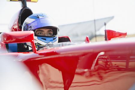 Focused formula one race car driver wearing helmet, looking away LANG_EVOIMAGES