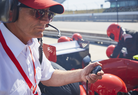 Manager with stopwatch timing formula one pit stop practice session LANG_EVOIMAGES