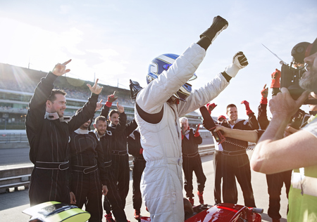 formula one: Formula one racing team and driver cheering, celebrating victory on sports track