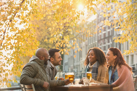alcohol series: Friends drinking beer at outdoor autumn cafe LANG_EVOIMAGES