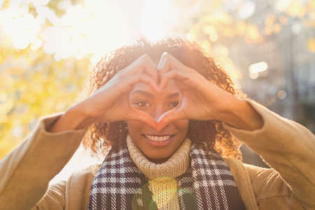 Portrait smiling young woman forming heart-shape with hands