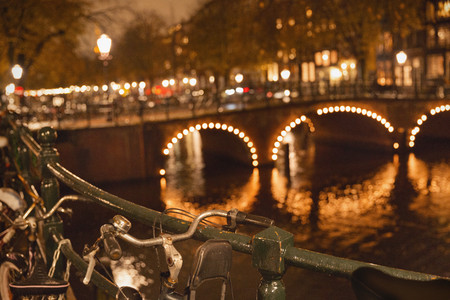 faerie: Bicycles and fairy lights along bridge over canal at night, Amsterdam