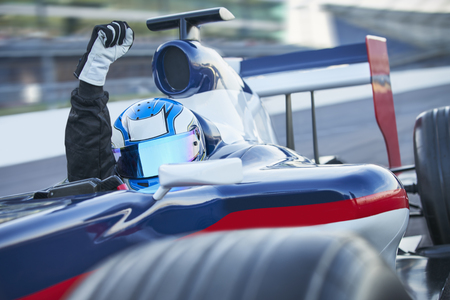 Portrait formula one race car driver wearing helmet and cheering with fist on sports track LANG_EVOIMAGES
