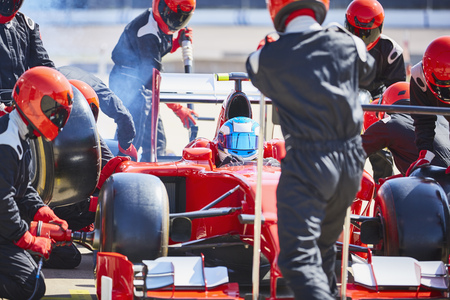 Pit crew working on formula one race car in pit lane LANG_EVOIMAGES