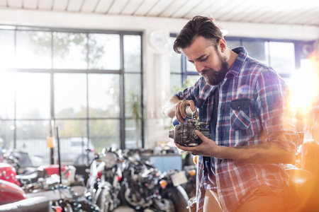 greasing: Motorcycle mechanic greasing engine part in workshop LANG_EVOIMAGES