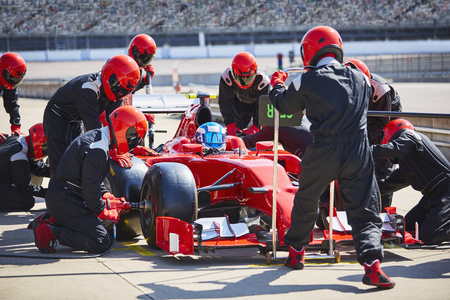 formula one: Pit crew working on formula one race car in pit lane LANG_EVOIMAGES