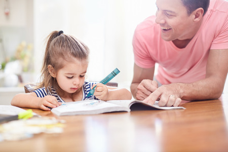 one parent: Father watching daughter coloring with crayon and coloring book at table LANG_EVOIMAGES