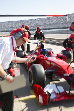 formula one: Manager with stopwatch timing pit crew replacing tires on formula one race car in practice session pit lane LANG_EVOIMAGES