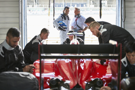 formula one: Formula one driver and manager talking behind pit crew working on race car in repair garage LANG_EVOIMAGES