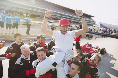 formula one: Formula one racing team carrying driver on shoulders, celebrating victory on sports track