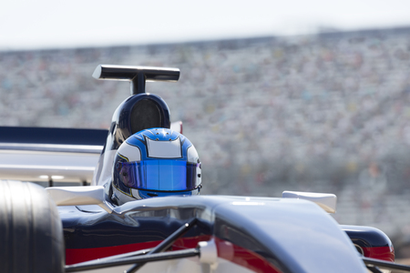 Formula one race car driver wearing helmet on sports track