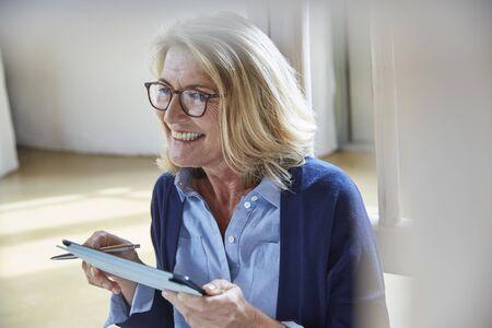 silver surfer: Smiling senior woman using digital tablet LANG_EVOIMAGES