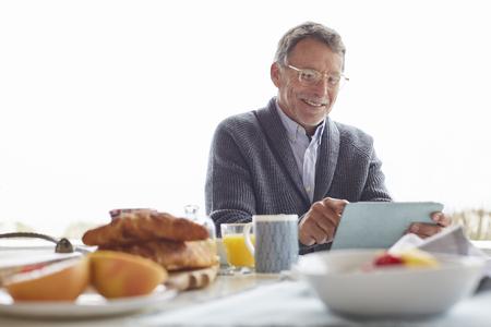 silver surfer: Senior man using digital tablet at patio breakfast